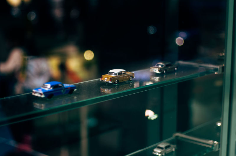Toy cars on glass shelf