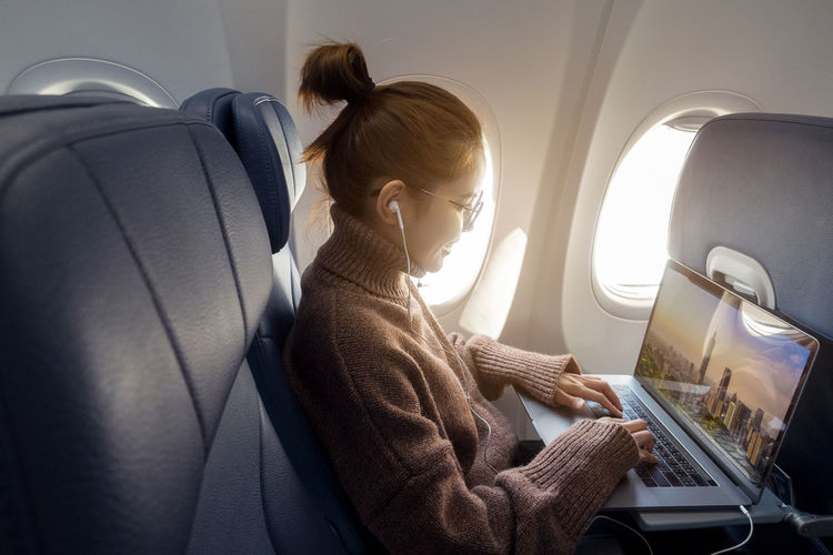 Side view of woman using laptop while sitting in airplane