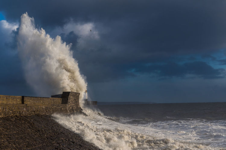 Waves splashing on shore against sky