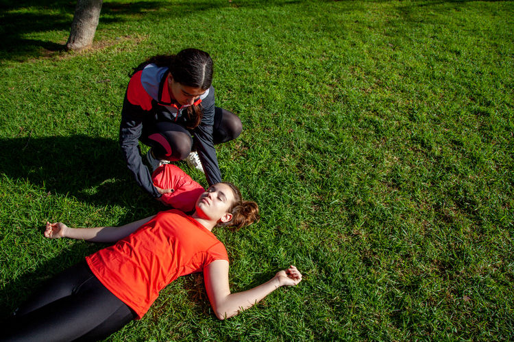 High angle view of woman giving cpr to girl lying on grassy land in park