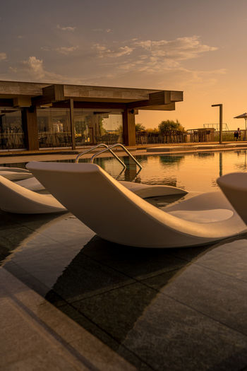 Swimming pool against sky during sunset
