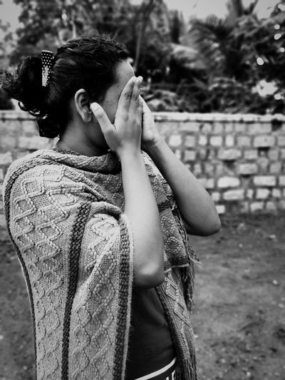 Woman with hands covering eyes standing on land against trees