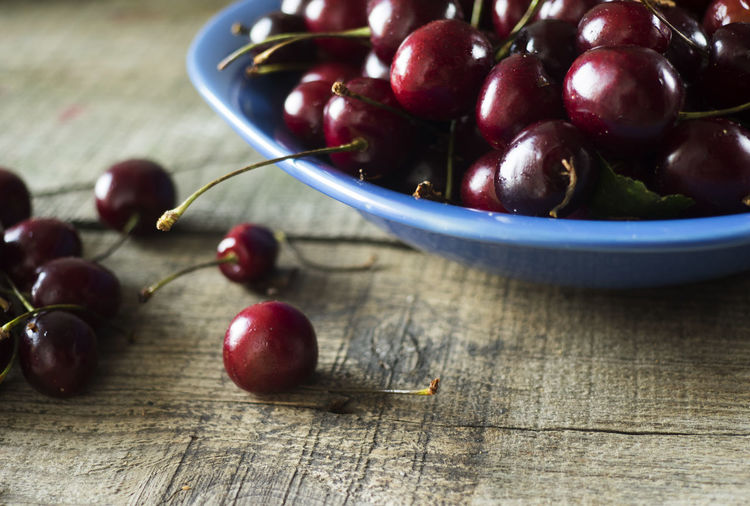 Close-Up Of Cherries In Bowl On Wooden Table