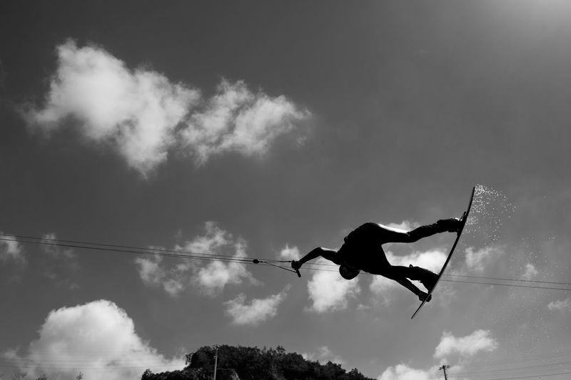 Low angle view of silhouette person wakeboarding in mid-air against sky