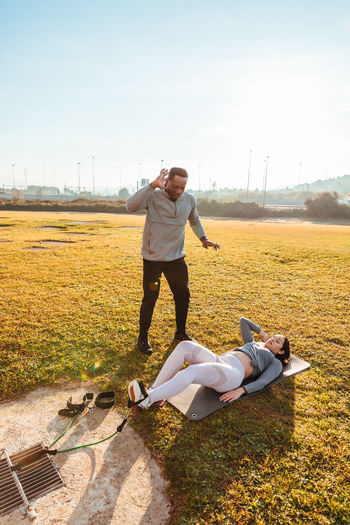 Woman exercising with instructor on land in sunny day