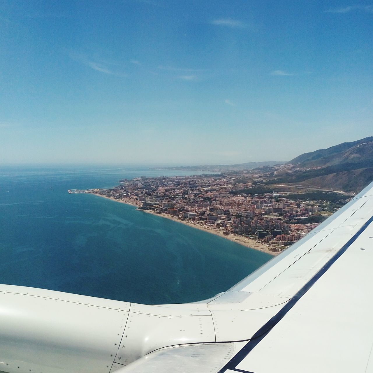 airplane, aerial view, transportation, journey, travel, landscape, mid-air, no people, scenics, beauty in nature, day, nature, sky, air vehicle, aircraft wing, mode of transport, flying, airplane wing, blue, outdoors, water, tranquil scene, mountain, tranquility, vehicle part, view into land, sea