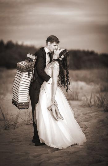 Couple kissing at beach against sky