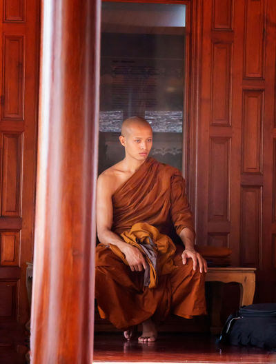 Full length of monk wearing traditional clothing while sitting against building