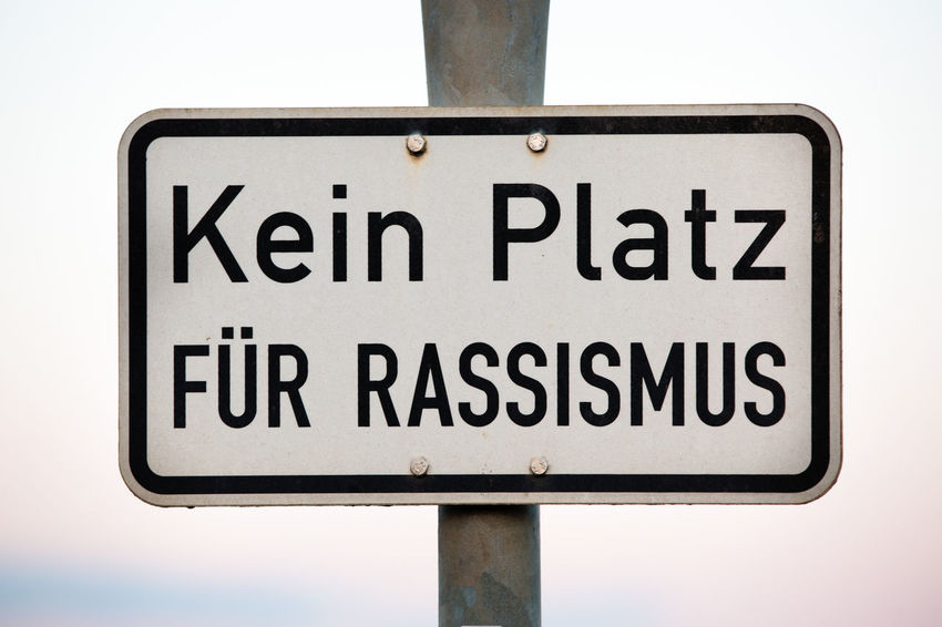 German Racism Statement Against Racism Capital Letter Close-up Communication Day Directional Sign Full Frame Germany Information Information Sign Message Multiculturalism No People No Racism Outdoors Rectangle Road Sign Sign Symbol Text Warning Sign Western Script