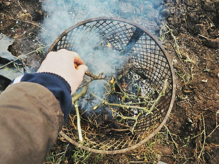 Cropped Image Of Hand Putting Sticks In Fire