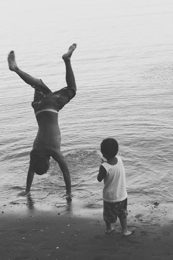 Boy looking at brother doing handstand on sea shore at beach