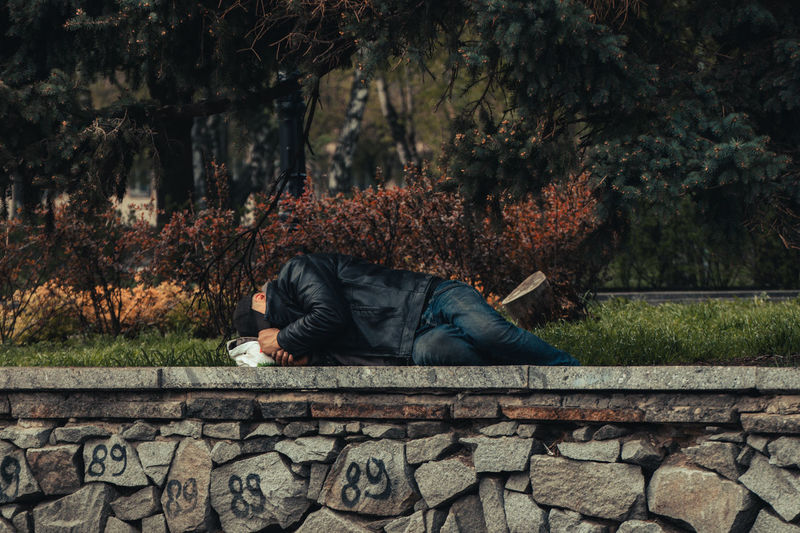 Man relaxing on retaining wall by park
