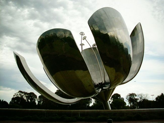 """Floralis Genéricais asculpturemade of steel and aluminum located inPlaza de las Naciones Unidas,Avenida Figueroa Alcorta,Buenos Aires, a gift to the city by theArgentinearchitectEduardo Catalano. Catalano once said that the flower """"is a synthesis of all the flowers and is both a hope that is reborn every day to open."""" It was created in 2002. The sculpture was designed to move, closing its petals in the evening and opening them in the morning. unykaphoto Buenos Aires emblematic places Buenos Aires Citytour floralisgenerica buenos aires sculptures Unykaphoto Buenos Aires Emblematic Places Buenos Aires Citytour Buenos Aires Sculptures Floralisgenerica"""