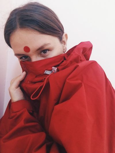 Portrait Of Woman Covering Her Face In Red Jacket Against White Wall