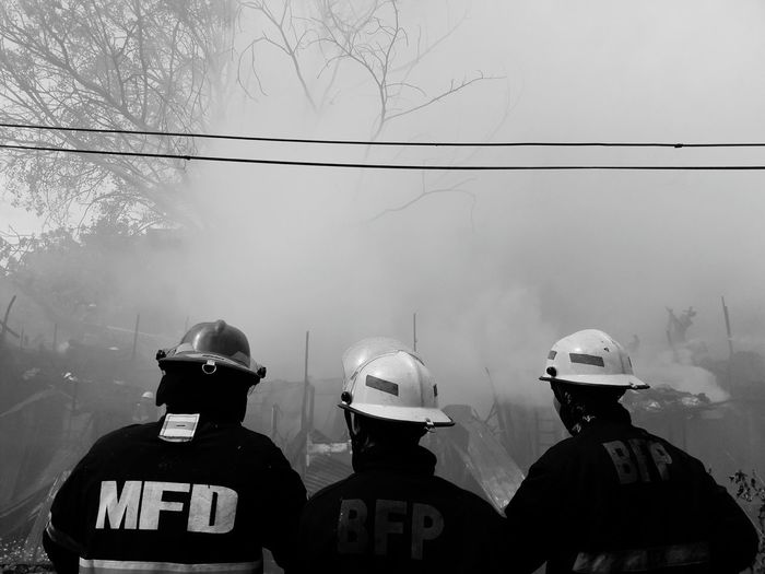 Checking the fire status. Manila, Philippines Blackandwhite Streetphotography Headwear Firefighter Togetherness Rear View Smoke - Physical Structure Extinguishing Rescue Worker