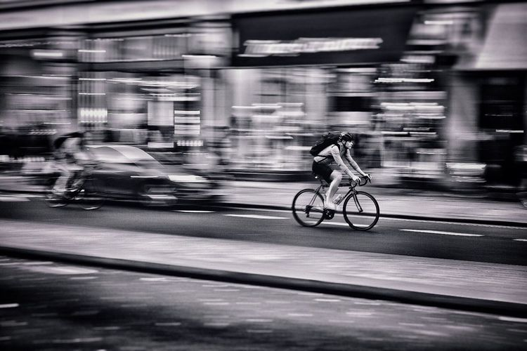 Man riding bicycle on city at night