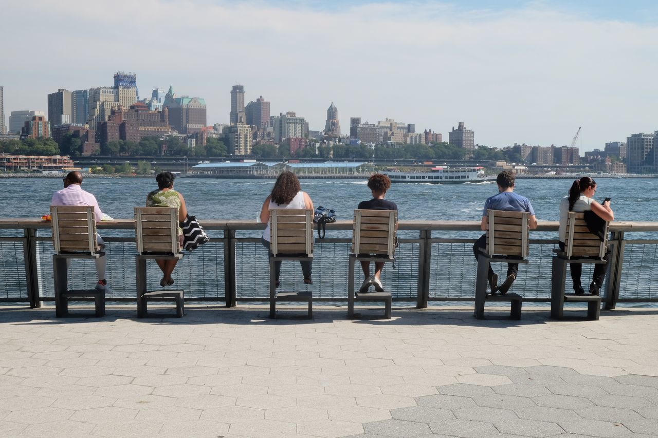 Rear View Of People Sitting On Chairs By River In City