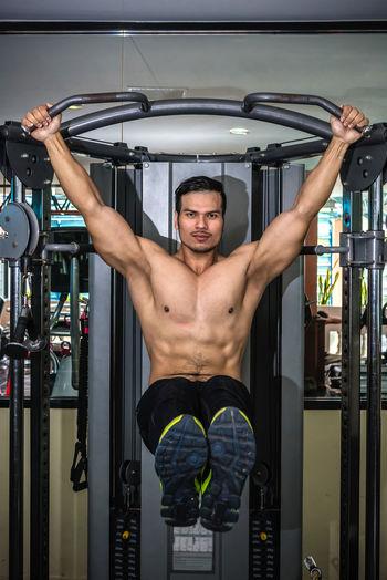 Shirtless muscular man exercising at gym