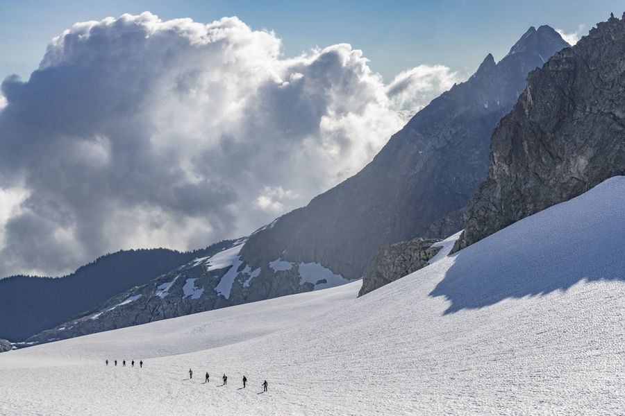 Expansive Mountaineer Mountaineering Rugged TEAMS Tiny Adventure Crossing Day Glacier Huge Immense Jagged Landscape Mountain Mountain Range Nature Outdoors Remote Scenics Sky Snow Sunlight Team Terrain