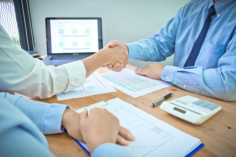 Midsection of businessman shaking hands with colleague in office
