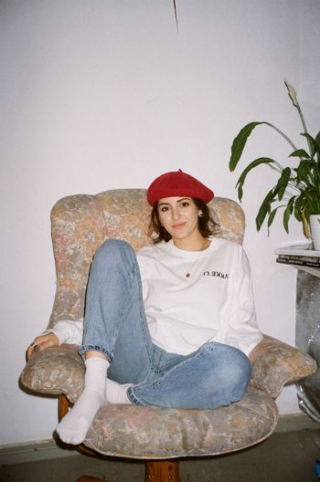 One Person Young Adult Sitting Casual Clothing Looking At Camera Front View Hat Young Women Indoors  Portrait Lifestyles Full Length Real People Leisure Activity Relaxation Clothing Seat Chair Hairstyle Beautiful Woman Contemplation Analog 35mm