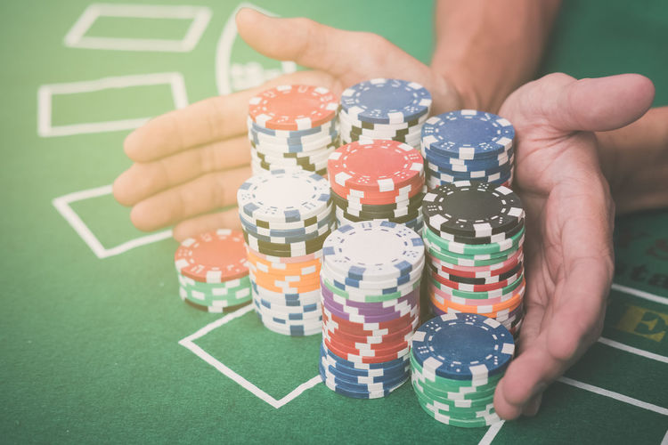 Close-Up Of Hands With Gambling Chips At Casino