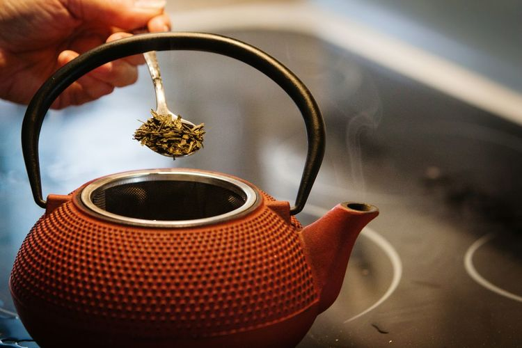 Cropped image of person adding herbs in tea kettle