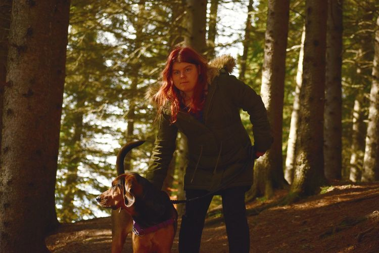 Portrait of woman with dog standing on land in forest