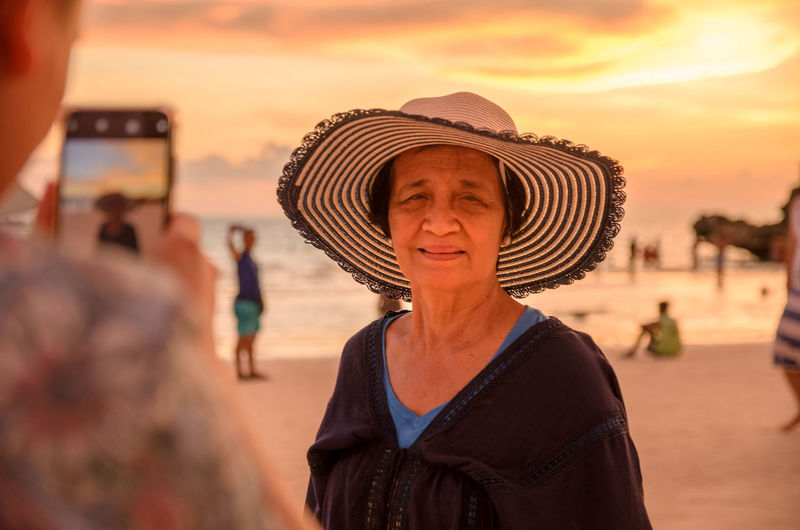 Portrait of woman wearing hat at beach against sky during sunset