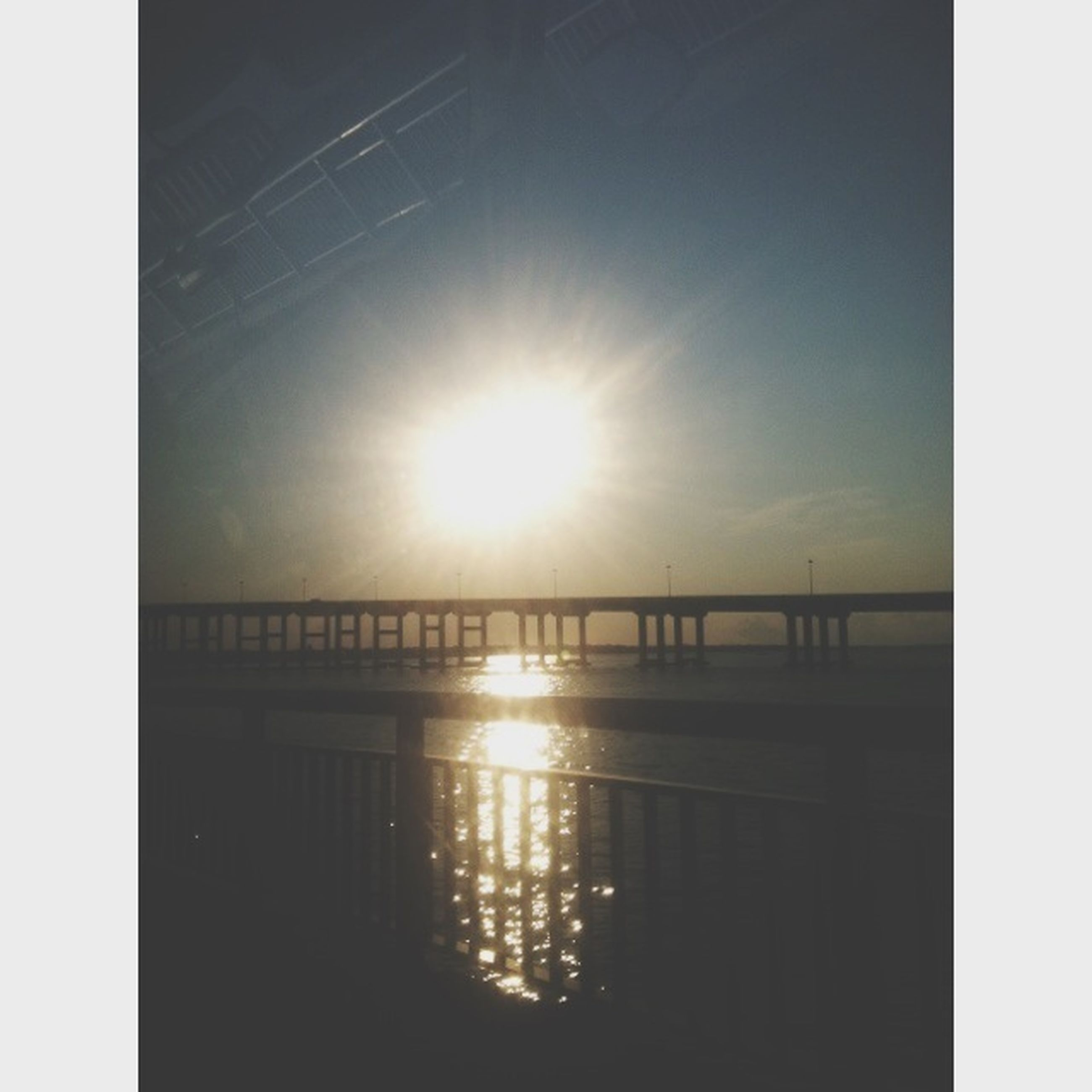 transfer print, sun, water, auto post production filter, built structure, sunlight, reflection, connection, sky, architecture, sunbeam, sunset, bridge - man made structure, sea, silhouette, lens flare, nature, tranquility, bridge, scenics