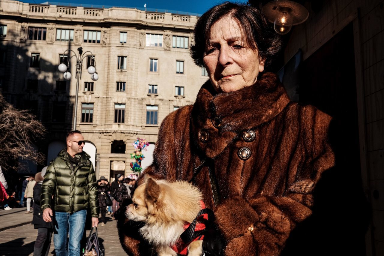 senior adult, city, street, city life, warm clothing, senior women, pets, dog, outdoors, real people, women, building exterior, lifestyles, one person, fur coat, adult, people, day, adults only