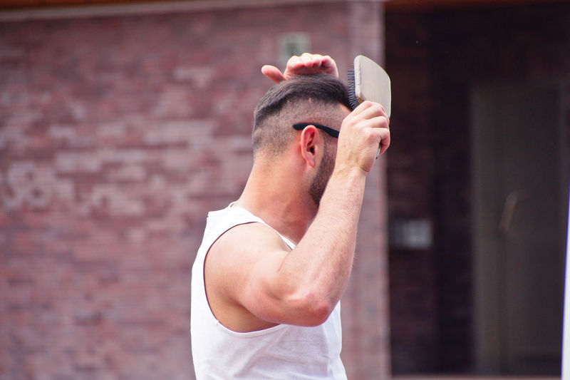 Side view of man brushing hair while standing against wall