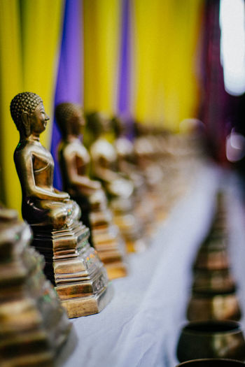 Golden buddha statues arranged on shelf at temple