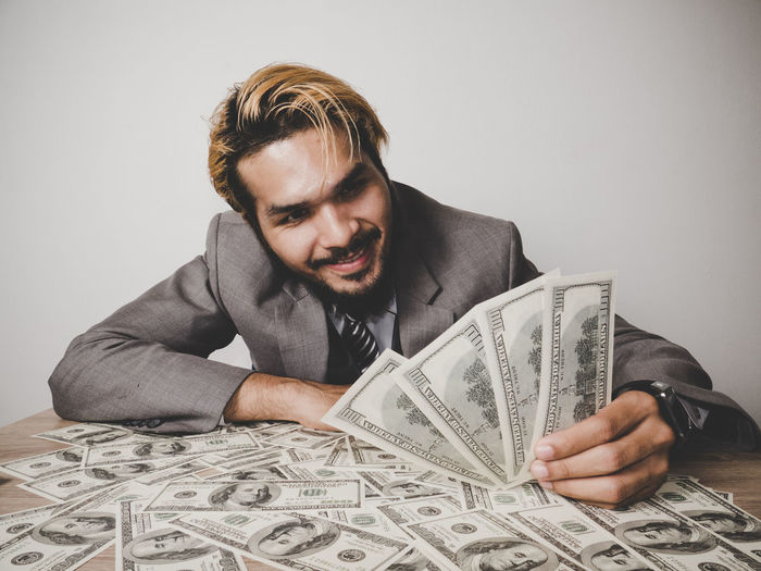 Smiling Businessman Looking At Paper Currency At Table