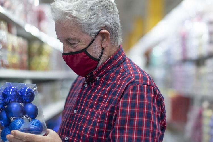 Senior man wearing mask standing at mall