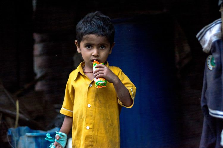 Portrait Of Boy Eating Food While Standing Outdoors