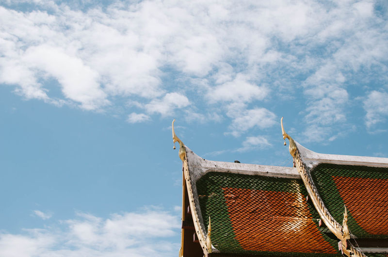 Low angle view of temple roof against cloudy sky