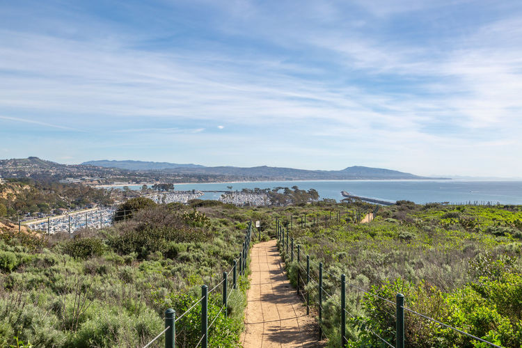 Looking along a walkway towards Dana Point and the Harbor, on a sunny day Sky Direction Scenics - Nature The Way Forward Plant Nature Water Footpath Tranquil Scene Sea Tranquility Beauty In Nature Day Cloud - Sky Horizon Architecture Land Built Structure Non-urban Scene No People Horizon Over Water Outdoors Dana Point, Ca California Pathway