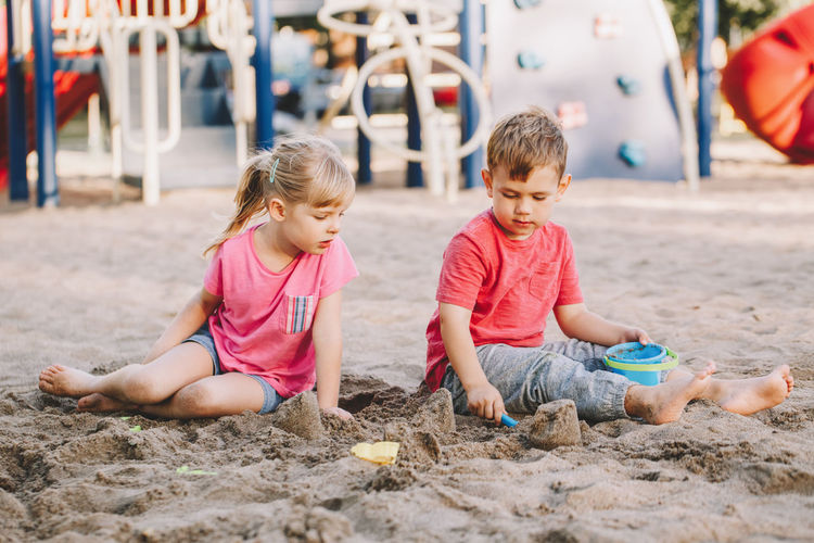 Cute siblings playing while sitting on sand