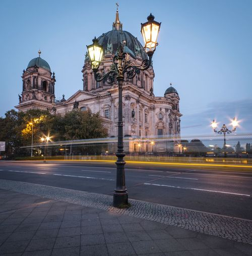 Illuminated street light in city against sky