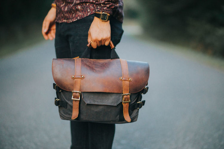 Man holding messenger bag made of canvas and brown leather