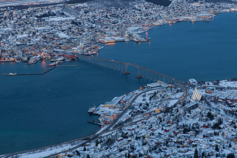 Aerial View Of Tromso Bridge Over Fjord Amidst Towns Against Sky
