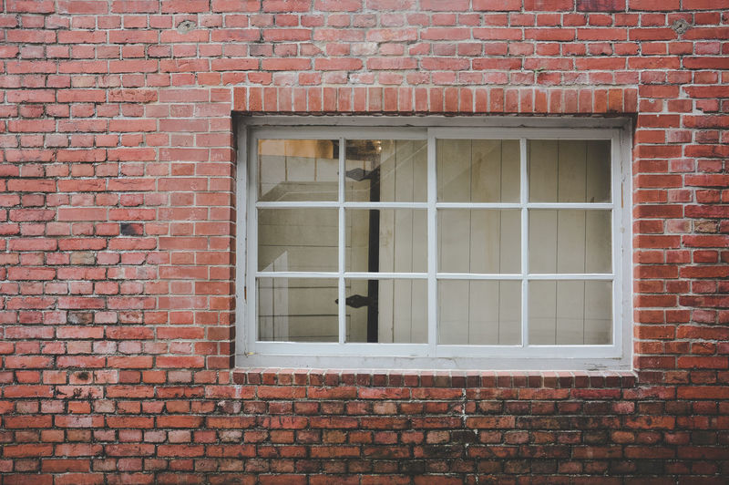 Old red brick wall texture background with classic white wooden frame and sash window with glass