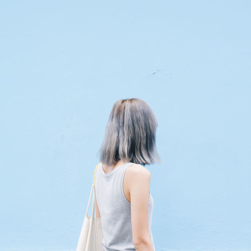 Woman walking standing against blue wall