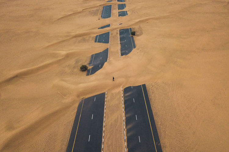 High angle view of silhouette person over road on sand in desert