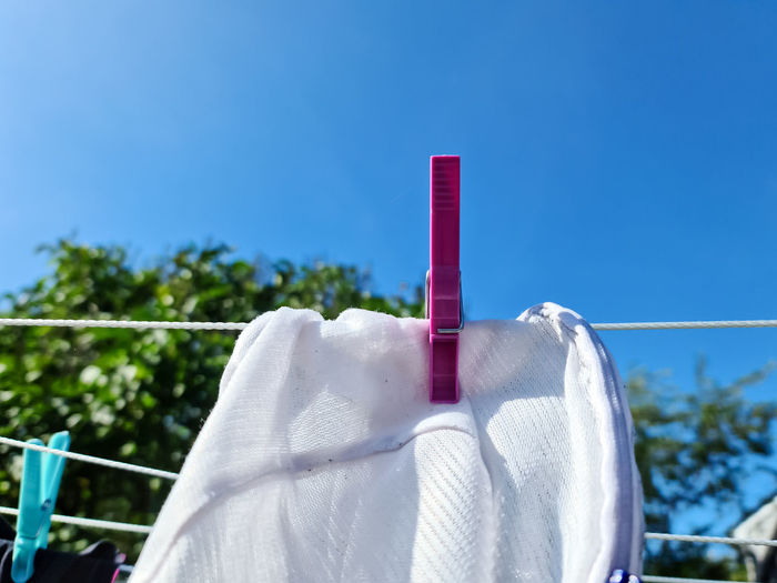 Close-up of clothes hanging on clothesline against blue sky