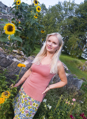 Blond woman standing by sunflowers in Estonia. Beautiful Woman Blond Hair Day Flower Lifestyles Nature One Person Outdoors People Plant Real People Standing Standing Sunflower Wall Young Adult Young Women