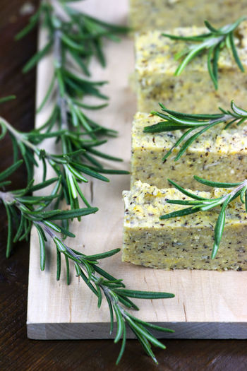 Close-up of rosemary and sliced polenta on cutting board