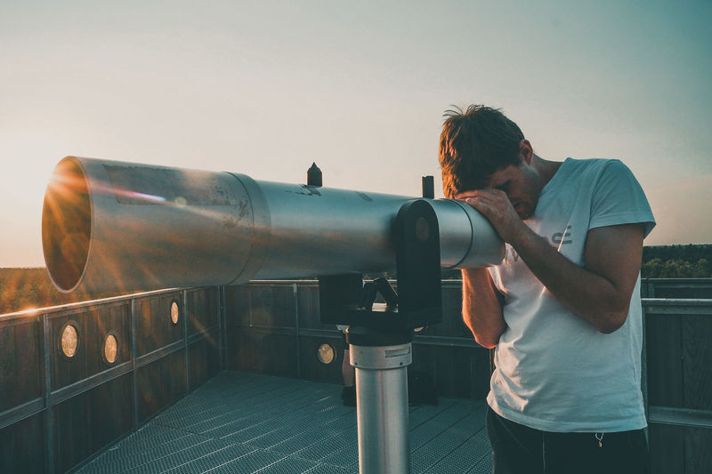 Man looking through telescope while standing against sky