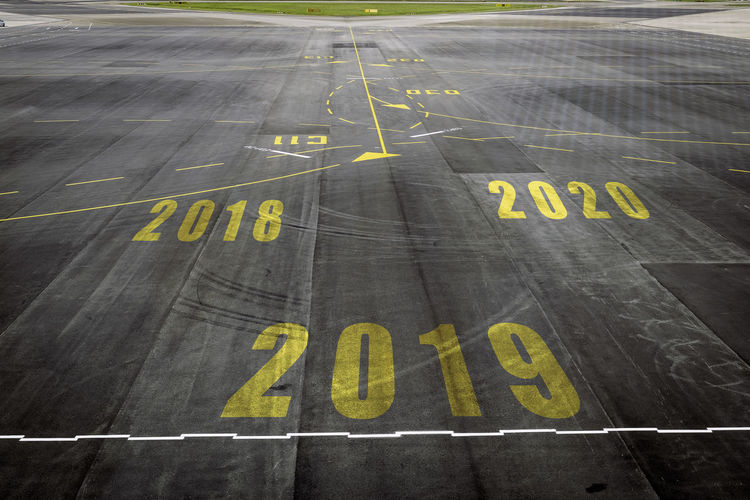 Closeup 2019 figures on the surface of the airport runway texture background. Air Vehicle Airplane Airport Airport Runway Capital Letter Communication Concrete Day High Angle View No People Number Outdoors Road Road Marking Safety Sign Symbol Text Transportation Western Script Yellow